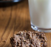 Chocolate no-bake cookies on a table with a glass of milk illuminated but sunlight coming oin from the right side.