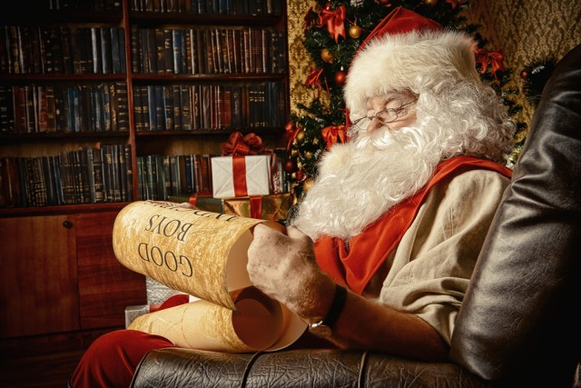 Santa Claus dressed in his home clothes sitting in the room by the fireplace and Christmas tree. He is reading a list of good boys and girls. Christmas. Decoration.