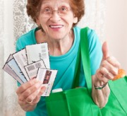 Excited Senior Woman Holding Coupons And Grocery Bag