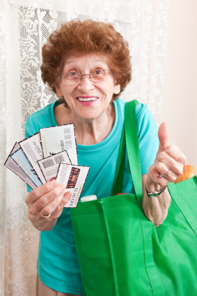 Excited Senior Woman Holding Coupons And Grocery Bag momspark.net