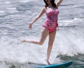 Female surfer at Morro Bay. CA's Morro Rock