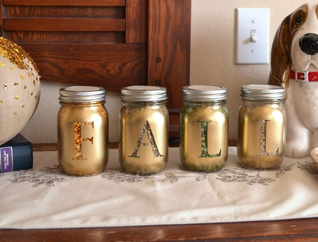 Mason jars are filled with a bounty of dried goods and dusted with gold for a beautiful table display!
