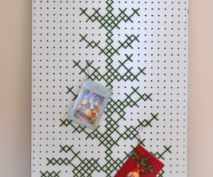 A big piece of pegboard meets cross stitch by way of yarn. Such a fun way to show off your holiday cards!